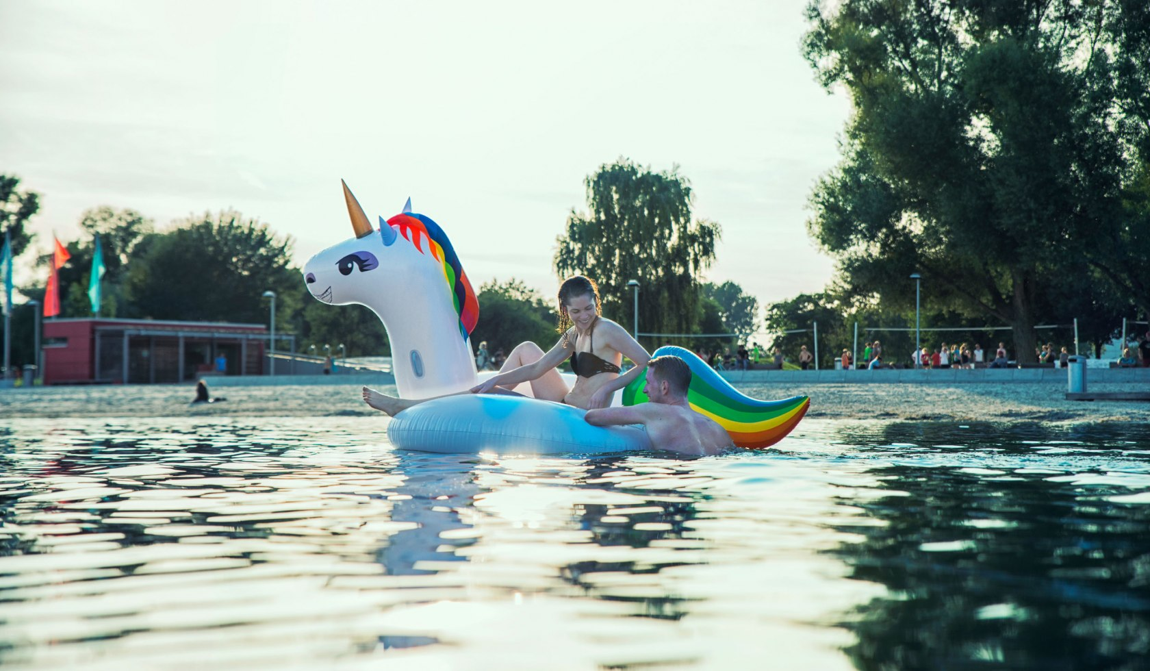 A young woman and a young man bathe in the Allersee with an inflatable unicorn