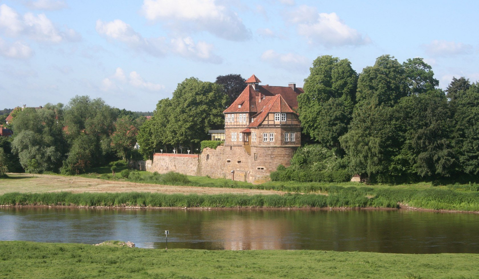The Weserenaissance castle in Petershagen behind the river.
