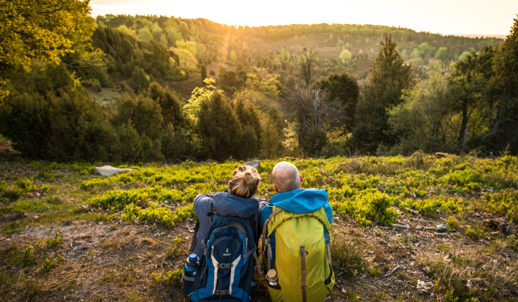two hikers seen from behind during a break in the Lüneburger Heide