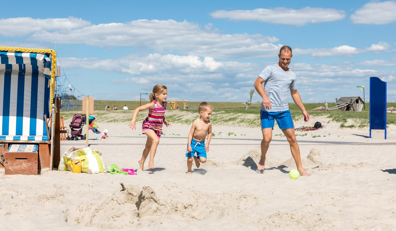 Father with a boy and a girl at the beach playing football