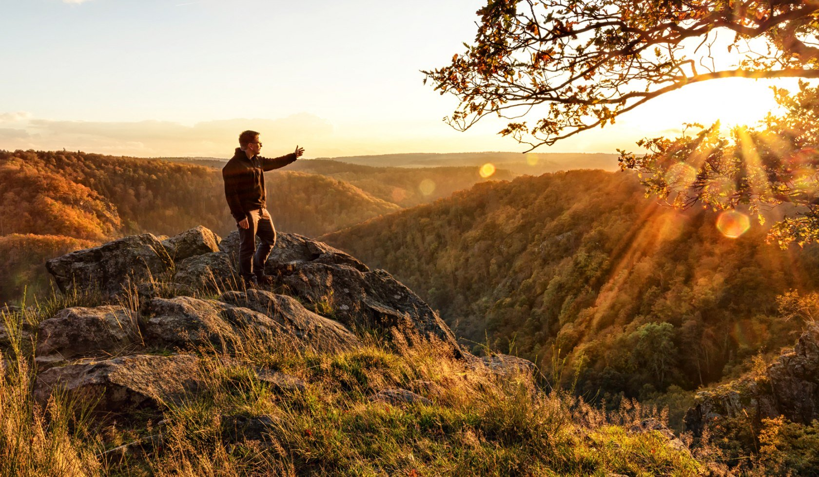 Man stands on mountain and stretches his arm out to the valley