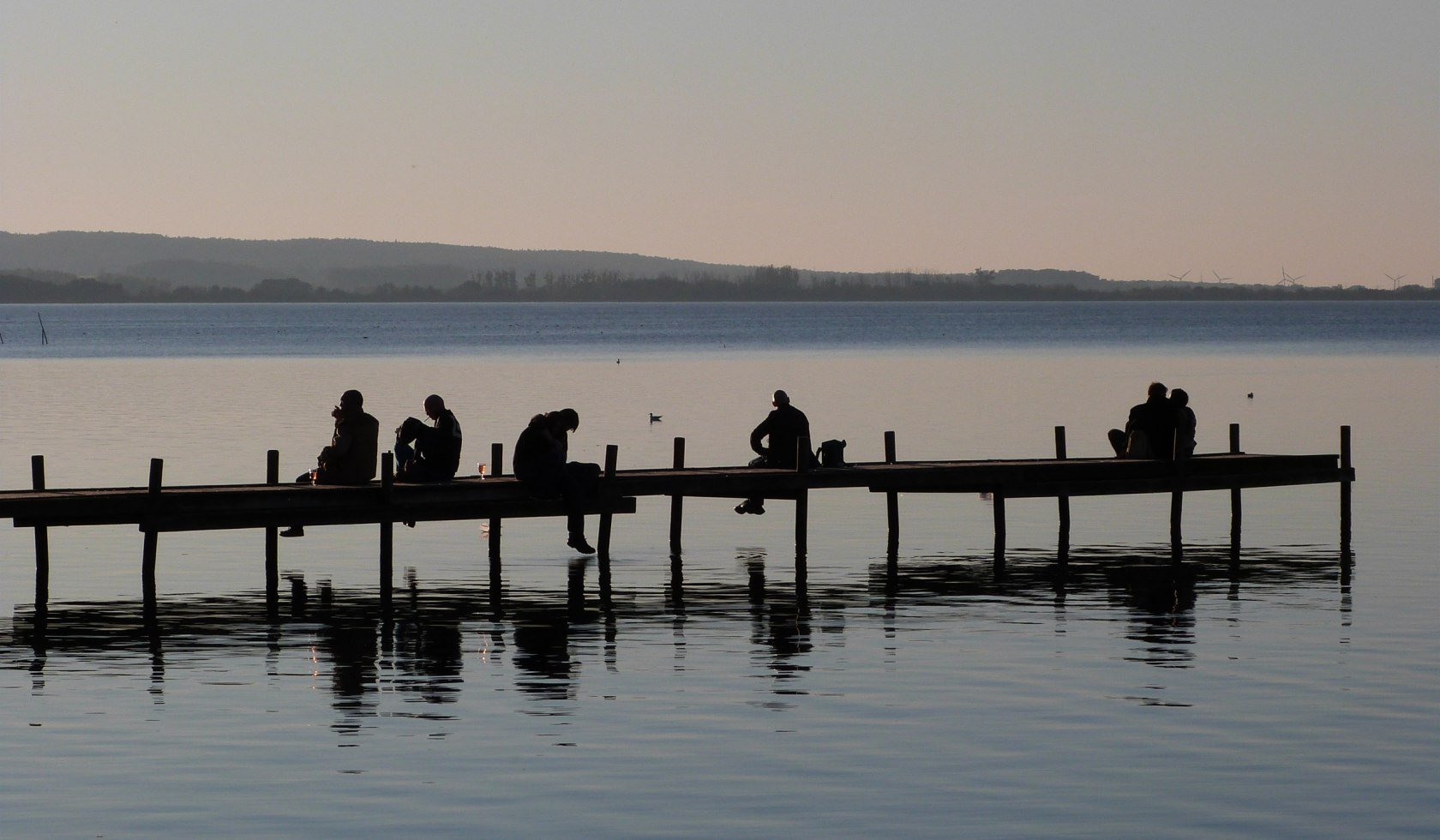 People sitting on a jetty in Steinhude in the evening light