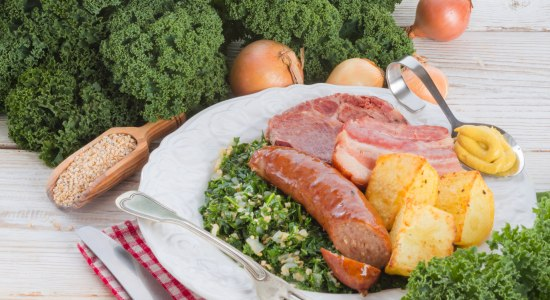 The plate is stocked with kale, pinkel, potatoes and smoked pork.